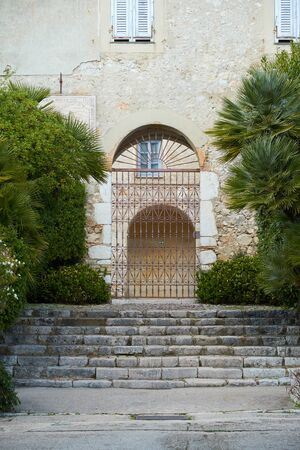 Gates and stone stairs of the Monastery Monastere de Cimiez in Nice, France. There is french text on the wall that is translated as average time. Stock Photo