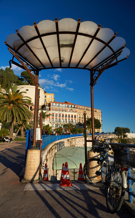 Nice, France - April 04, 2019: Entrance to the restaurant on the beach. Bellanda tower and hotel Suisse are on the background.