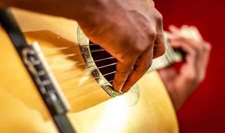 Guitarist hits the strings of the guitar, close up black men fingers playing music on guitar