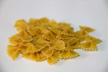 A close-up view of many whole grain Farfalle pasta uncooked with white backgound photo