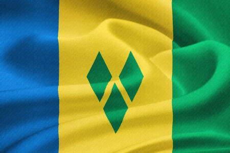 windward:  flag of Saint Vincent and the Grenadines waving in the wind. Silk texture pattern Stock Photo