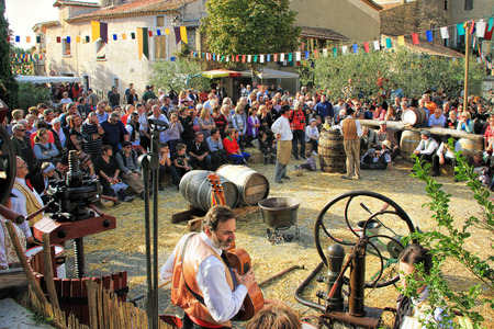 CHUSCLAN, FRANCE - October13, 2013: Traditional Wine Pressing and juice tasting using a manual grape crushing machine during the festival grape harvest of the history October 12 and 13, 2013, in Chusclan, France.