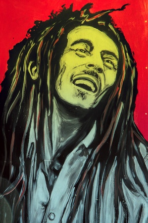 jamaica: SETE, FRANCE  - SEPTEMBER 21, 2014: Graffiti portrait of Bob Marley, a famous Jamaican reggae singer-songwriter and guitarist on the wall of Sete, south of France.