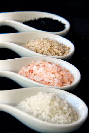 Variety of Different Sea Salts in spoons on on a black slate stone background