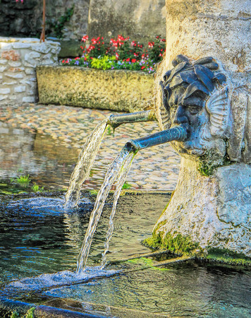Ancient fountain in  Tavel village in the south of France photo