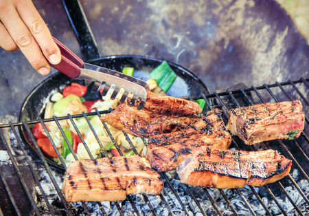 broiling: spare ribs and vegetable grill pan on a grill Stock Photo