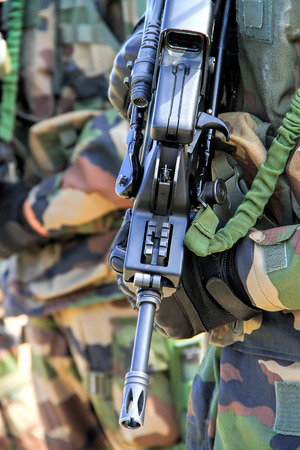 guerilla warfare: Ready for combat: Close up of a soldier with a gun Stock Photo