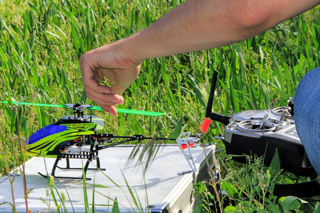 controlled: Piloting Radio controlled helicopter  with remote control.