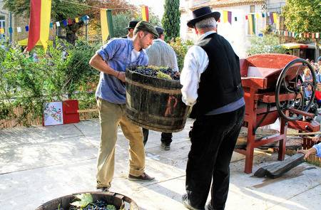 period costume: CHUSCLAN, FRANCE - October13, 2013: Traditional Wine Pressing using a manual grape crushing machine during the 15th festival \grape harvest of the history\ October 12 and October 13, 2013, in Chusclan, France.