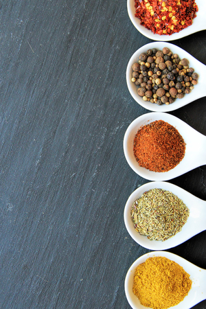 black peppercorn: variety of spices on a black slice. From  up to down: espelette chili, Black Peppercorn, paprika, Provencal Herbs, curry powder Stock Photo