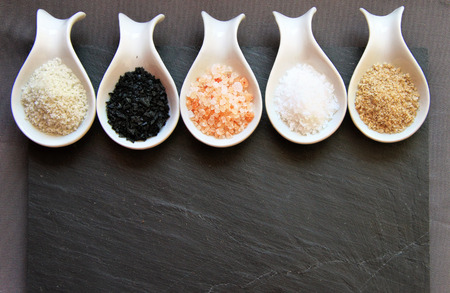 salt: Variedad de diferentes sales de mar en cucharas en sobre un fondo de piedra de pizarra negro
