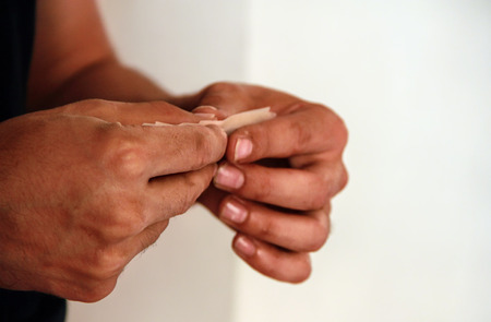 hashish: Close up of male hand rolling hashish joint Stock Photo