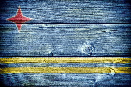rough sea: flag of Aruba painted on old grungy wooden  background Stock Photo