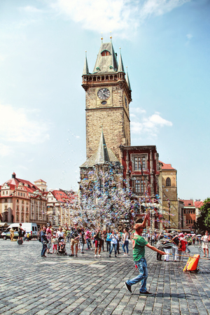 PRAGUE, CZECH REPUBLIC - JUNE 06, 2016: Unidentified young man makes soap bubbles in Old Town Square (Staromestske namesti) in Prague, Czech Republic. Prague historical centre has an area of 866 hectares and was added to the list of UNESCO World Heritage  Editorial
