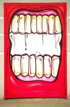LAUDUN, FRANCE - May 08, 2014: Graffiti mouth painted on the door of the Forum sport center in Laudun, France.