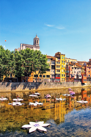 GIRONA, SPAIN - MAY 10, 2015: Flowers and houses reflection in Onyar River during Festival of floral decorations in Girona, Catalonia, Spain