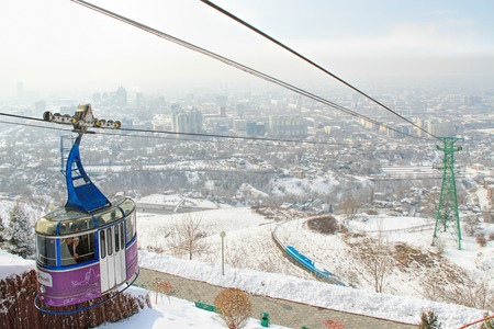 ALMATY, KAZAKHSTAN - MARCH 10, 2014: Funicular with tourists and view of the foggy city of Almaty, Kazakhstan