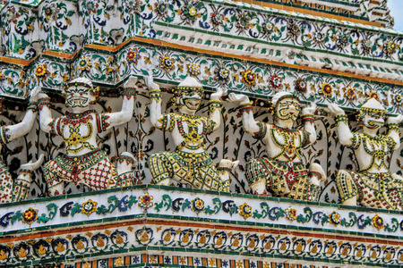 Giant sculptures around the central prang, a stupa-like pagoda encrusted with colorful glazed porcelain tiles and seashells in Wat Arun Ratchatharam or Temple of the Dawn, Bangkok, Thailand