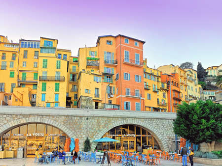 Menton, France - February, 22, 2020: colorful houses in old town in Provence village Menton, France, French Riviera, sunset evening view Editorial
