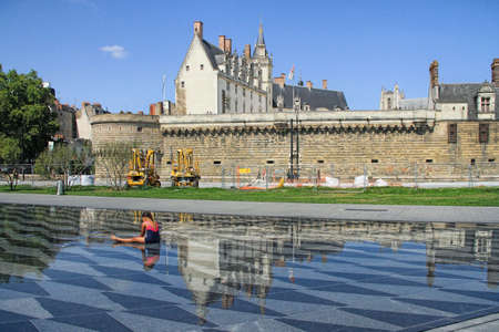 NANTES, France - August, 18, 2018: Girl sitting in the water mirror fountain with the View on the castle of Dukes of Brittany in Nantes city in France