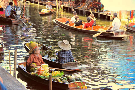 Bangkok, Thailand - May 08, 2018: unidentified tourists and traditional vendors on the famous floating market Damnoen Saduak in Bangkok. It is a traditional market on the khlongs, where they sell goods and food from the boats. Editorial