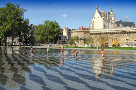 Nantes, France - August, 18, 2018: View on the castle of Dukes of Brittany with water mirror fountain and tourists in Nantes city in France