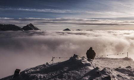 inversion: Beautiful winter mountain landscape. Man sitting on top of the mountain. Tatry Stock Photo