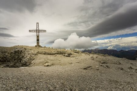 Rocky landscape with a cross on the summit of Sass Pordoi. Dolomites. Italy.