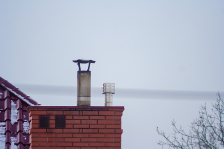 a brick chimney and a pipe ending against a gray sky background