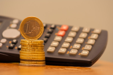 Close up of stacked coins and 1 euro on top, calculator in the background