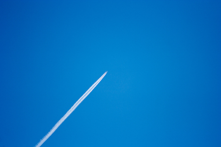 streak of an airplane flying in the clear blue sky Stock Photo