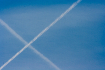 a streak of intersection of two  planes flying in the clear blue sky