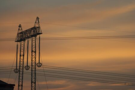 high voltage pole and orange sky during sunset