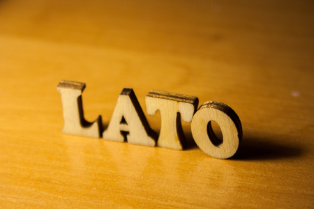 The polish word 'lato' made of wooden letters. wood inscription on table