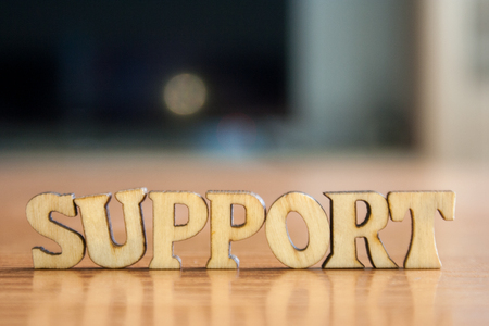 The word support made of wooden letters. wood inscription on table Stock Photo