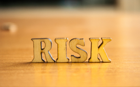 The word risk made of wooden letters. wood inscription on table