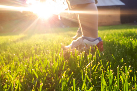 The legs of a three-year-old child who is standing on green grass. The sun's rays in the background