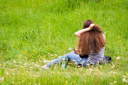 A young girl sits backwards on a green meadow and improves her dark hair