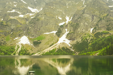 A beautiful view of the 'Morskie Oko' lake in the Polish Mountains in the Tatras. Green trees are reflected from the water's surface. A beautiful landscape from the perspective of a tourist.