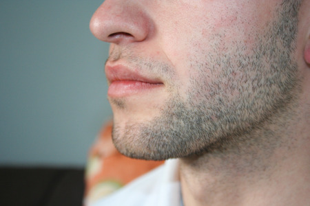 A man's face with a slight beard. A few days beard on the guy's chin. Macro picture taken from the profile.