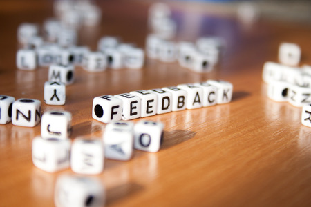 The word FEEDBACK made of white plastic blocks on the table. Letter concept. Stockfoto