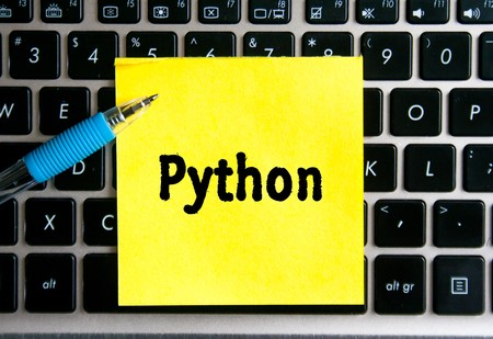 "The inscription ""PYTHON"" on a yellow sheet of sticker paper on the background of a computer keyboard."