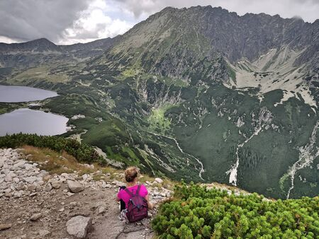 The girl sits back in the mountains and admires the views. The woman is looking at the Five Pond Valley in Poland in the Tatra Mountains. Фото со стока