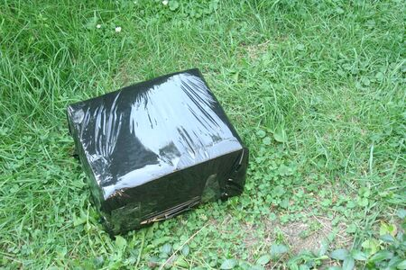 A parcel in a black box lying on the grass. Curier posts. Receiving parcels.