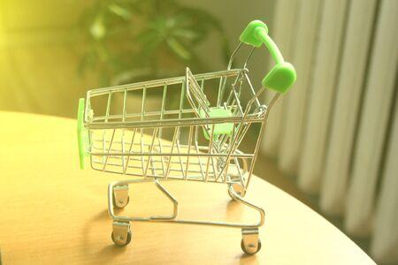 miniature shopping cart on wooden mock Zdjęcie Seryjne
