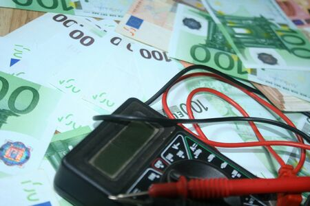 Multimeter on the euro banknotes background. The concept of electricity and electricity bills. Foto de archivo