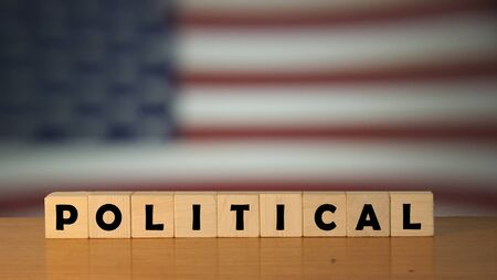 POLITICAL USA message word on a wooden desk on cube blocks with a USA flag background Stock Photo