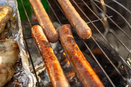 Grilling sausages on the grill grate, close-up. Grilling food, bbq, barbecue