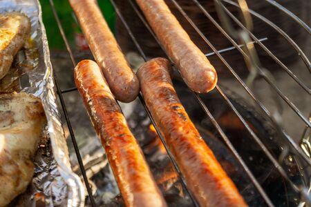 Griller des saucisses sur la grille du gril, gros plan. Griller des aliments, barbecue, barbecue