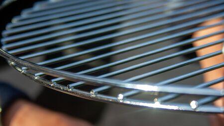 Closeup new metal grill grate. Empty clean grid. Picnic tools.